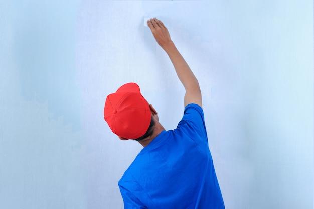 Giovane uomo asiatico del costruttore che applica intonaco del mastice sulla parete bianca. intonaco da parete a parete di finitura.