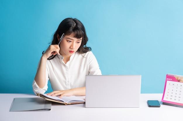 Giovane donna asiatica di affari che lavora all'azzurro