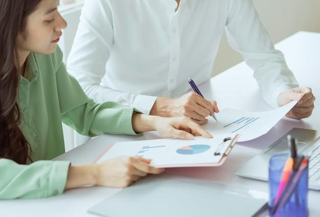 Giovani coppie asiatiche di affari che lavorano insieme, completando il lavoro assegnato
