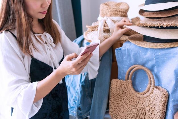 Giovane imprenditore asiatico che controlla l'equilibrio delle azioni e che scrive nota sul taccuino. vendita online, e-commerce, business e tecnologia, nuovo concetto normale