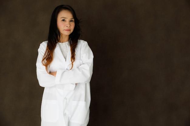 Giovane donna d'affari asiatica con un elegante cappotto bianco che guarda la telecamera e sorride su uno sfondo grigio scuro