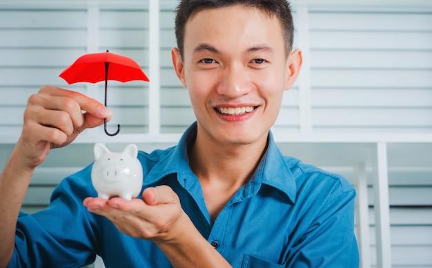 Giovane ombrello asiatico della tenuta dell'uomo di affari per il porcellino salvadanaio di protezione.