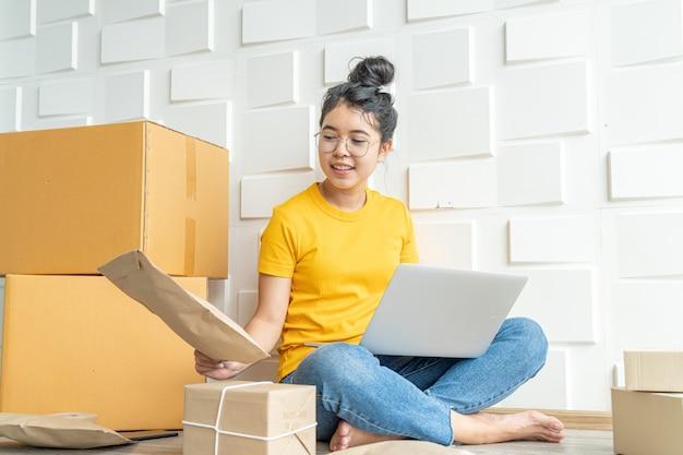 La giovane impresa asiatica avvia il proprietario del venditore online utilizzando il computer per controllare gli ordini dei clienti dall'e-mail o dal sito web e preparare i pacchetti