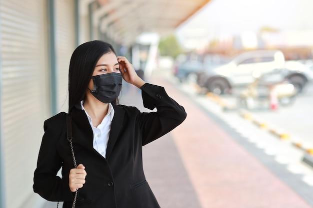 Giovane donna asiatica di affari in vestito nero di affari con la mascherina protettiva per l'assistenza sanitaria che cammina sulla strada all'aperto e alla ricerca pubblica