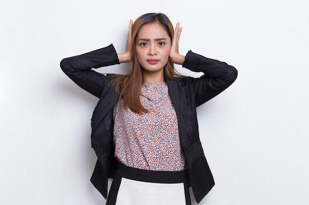 Giovane donna d'affari asiatica che copre entrambe le orecchie con le mani isolate su sfondo bianco
