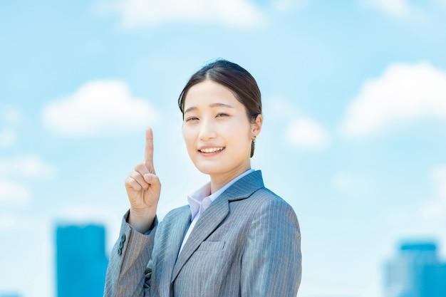 Giovane donna d'affari asiatica che punta il dito indice