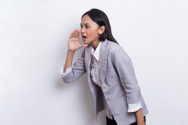 Giovane donna d'affari asiatica che grida e urla annunciando isolato su sfondo bianco