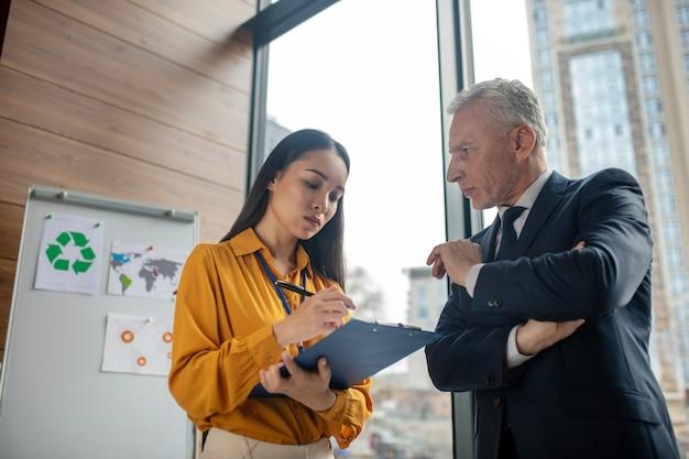 Giovane donna asiatica di affari con capelli lunghi che prendono appunti mentre il suo capo parla