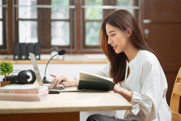 La giovane donna asiatica di affari che lavora con internet facendo uso del computer portatile si siede all'appartamento