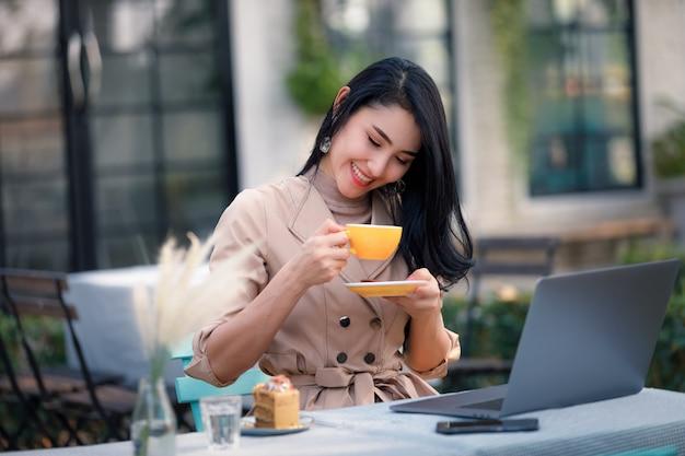 Giovani donne asiatiche di affari e indipendente che si siedono sulla tavola di legno nel giardino e che bevono caffè bevente