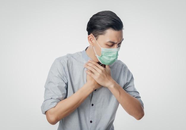 Giovane uomo d'affari asiatico in maschera igienica che soffre di mal di gola, 2019-ncov o coronavirus. malattie respiratorie sospese nell'aria come il combattimento e l'influenza del pm 2.5. colpo dello studio isolato sulla parete bianca