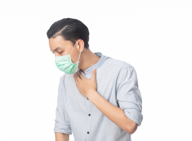 Giovane uomo d'affari asiatico in maschera igienica che soffre di mal di gola, 2019-ncov o coronavirus. malattie respiratorie sospese nell'aria, come i combattimenti di pm 2.5 e l'influenza. colpo dello studio isolato sulla parete bianca