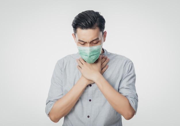 Giovane uomo d'affari asiatico nella maschera igienica sofferenza mal di gola, coronavirus. malattie respiratorie sospese nell'aria come il combattimento e l'influenza del pm 2.5. colpo dello studio isolato su fondo bianco.