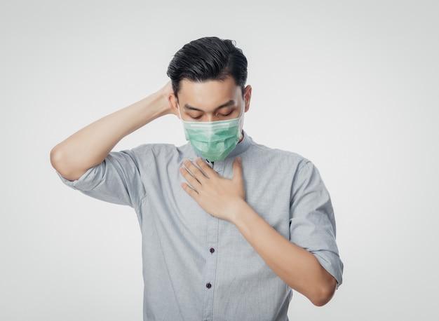 Giovane uomo d'affari asiatico in maschera igienica che soffre di mal di gola e che ha influenza, 2019-ncov o coronavirus. malattie respiratorie sospese nell'aria come il combattimento con pm 2.5. colpo dello studio isolato sulla parete bianca