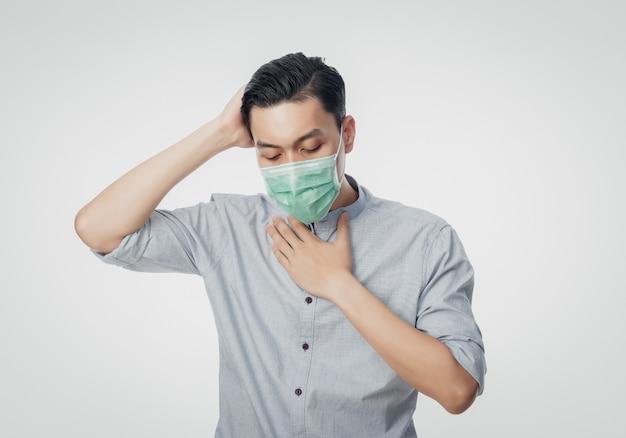 Giovane uomo d'affari asiatico in maschera igienica che soffre di mal di gola e che ha influenza, 2019-ncov o coronavirus.