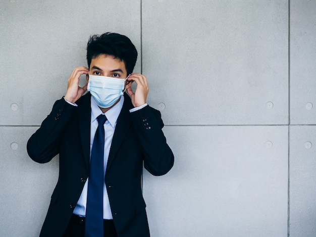 Giovane imprenditore asiatico in tuta che indossa la maschera medica sul muro grigio sfondo in ufficio