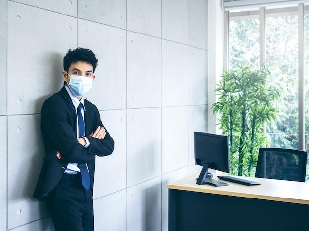 Giovane uomo d'affari asiatico in vestito che indossa la maschera facciale medica in piedi con le braccia incrociate sul muro grigio