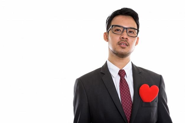 Giovane uomo d'affari asiatico pensando con cuore rosso sul suo vestito