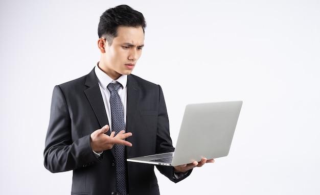 Giovane uomo d'affari asiatico utilizzando laptop su bianco