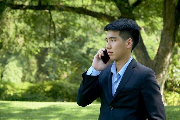 Giovane uomo d'affari asiatico che cammina nel parco