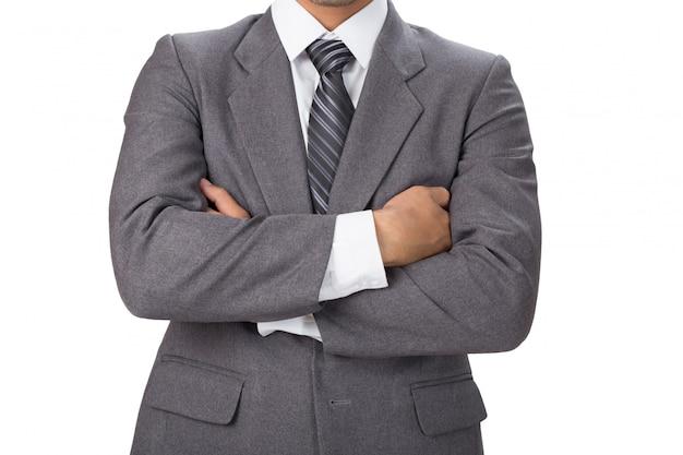 Giovane uomo d'affari asiatico che indossa vestito grigio che sta con le armi piegate sopra la parete bianca