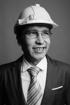 Giovane uomo d'affari asiatico che indossa elmetto protettivo
