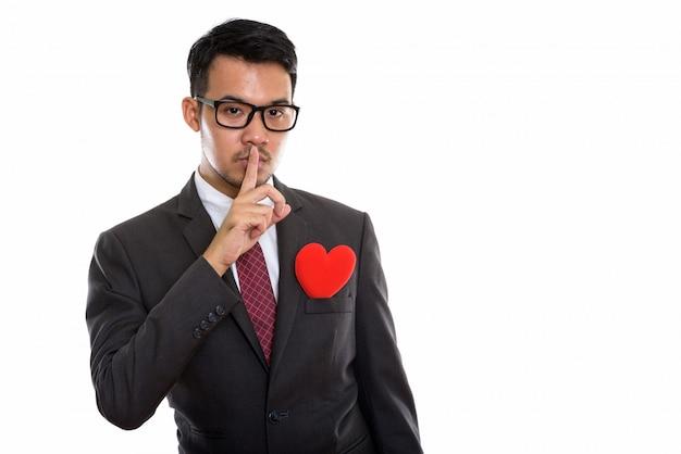 Giovane uomo d'affari asiatico con un dito sulle labbra e cuore rosso sulla sua tuta