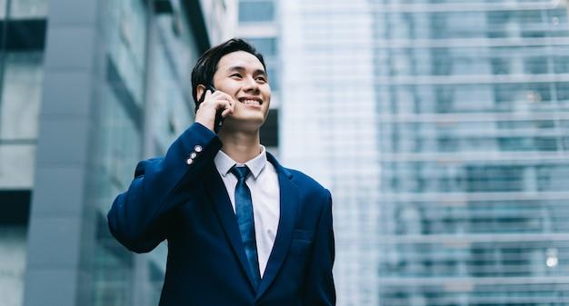 Giovane uomo d'affari asiatico con edificio in vetro