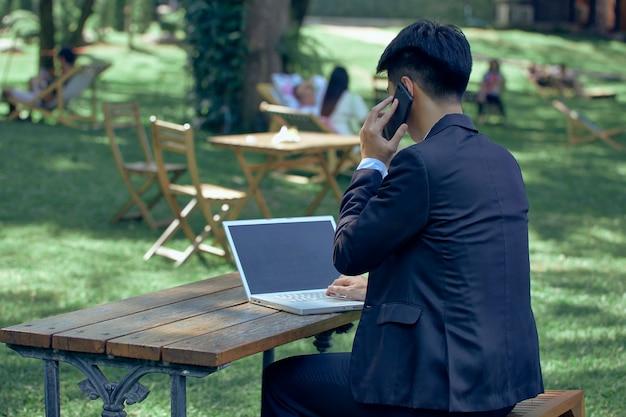 Giovane uomo d'affari asiatico con laptop e notebook che lavorano nel parco con chat video sul computer portatile con un collega mentre si è seduti all'aperto in giardino. affari e tecnologia