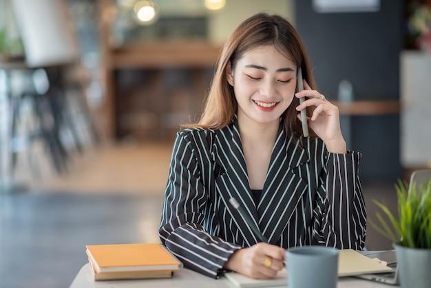 Giovane donna di affari asiatica bella affascinante sorridente e parlando al telefono cellulare in ufficio