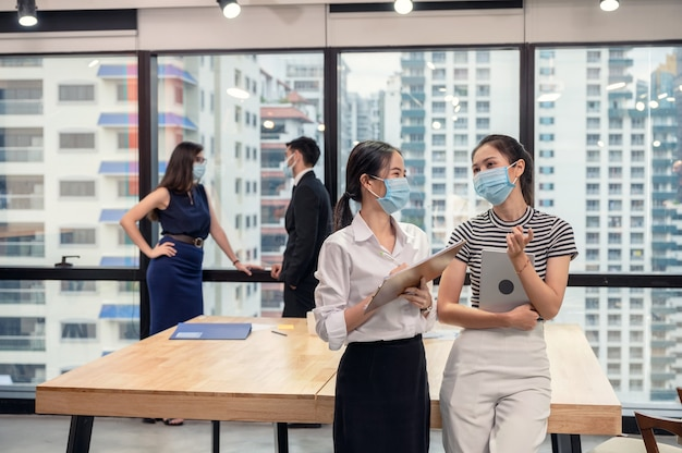 Giovane collega asiatico della donna di affari che indossa la maschera per il viso e parla nel nuovo ufficio normale, discutendo esecutivo caucasico
