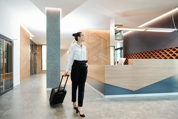 Giovane imprenditrice asiatica in abiti da cerimonia tirando la valigia mentre si muove lungo la lounge dell'hotel con bancone della reception sullo sfondo