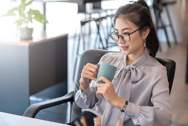 La giovane donna di affari asiatica ha il piacere di guardare il lavoro sul proprio tablet e il caffè preferito in ufficio.