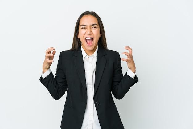 Giovane imprenditrice asiatica isolata sul muro bianco urlando di rabbia.