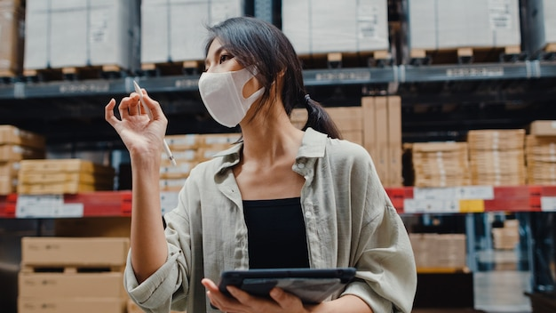 Responsabile della giovane donna di affari asiatica che indossa il magazzino della maschera per il viso utilizzando l'inventario di controllo della tavoletta digitale