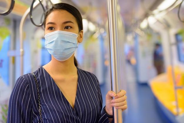 Giovane imprenditrice asiatica pensando con maschera per la protezione dallo scoppio del virus corona all'interno del treno