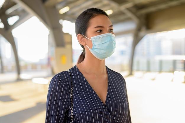 Giovane imprenditrice asiatica pensando con maschera per la protezione dallo scoppio del virus corona alla stazione dello skytrain