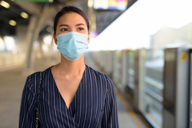 Giovane imprenditrice asiatica in attesa con maschera per la protezione dallo scoppio del virus corona alla stazione dello skytrain