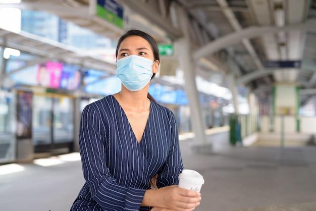 Giovane imprenditrice asiatica con maschera un caffè in movimento durante l'attesa alla stazione dello skytrain