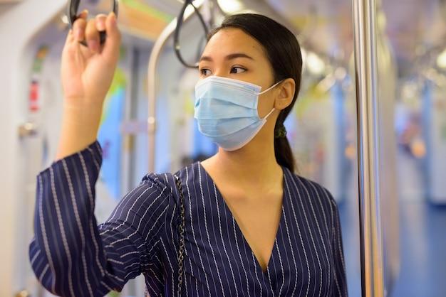 Giovane imprenditrice asiatica con maschera per la protezione dallo scoppio del virus corona pensando all'interno del treno
