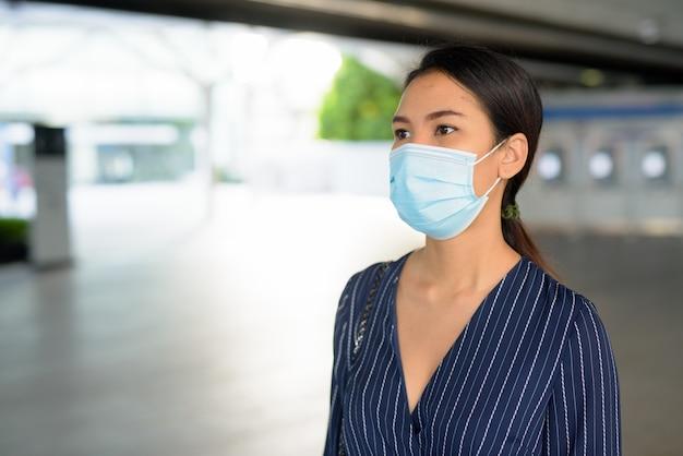 Giovane imprenditrice asiatica con maschera per la protezione dallo scoppio del virus corona a piedi dalla stazione ferroviaria