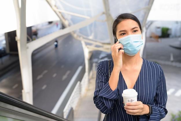 Giovane imprenditrice asiatica con maschera parlando al telefono mentre beve un caffè in movimento come la nuova normalità in città