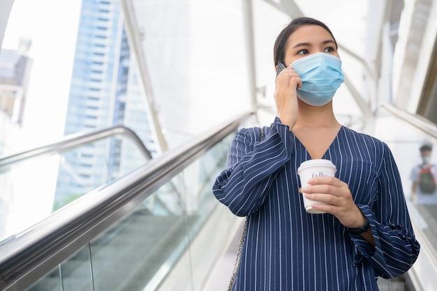 Giovane imprenditrice asiatica con maschera parlando al telefono con caffè in movimento come la nuova normalità in città all'aperto