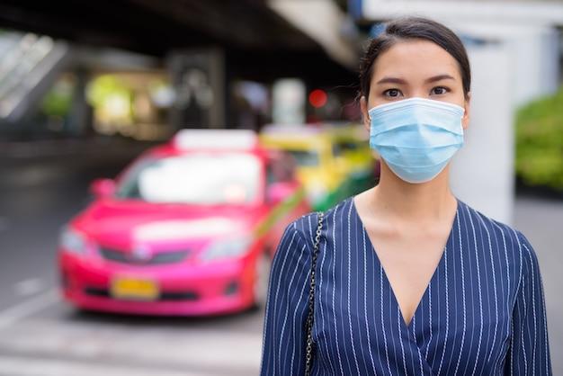 Giovane imprenditrice asiatica con maschera alla stazione dei taxi per le strade della città