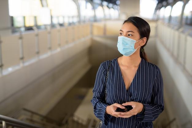 Giovane imprenditrice asiatica con maschera pensando mentre sale la stazione dello skytrain