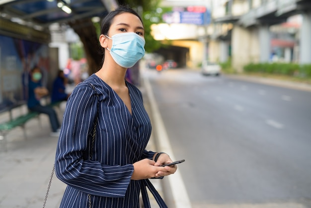 Giovane imprenditrice asiatica con maschera pensando mentre si utilizza il telefono alla fermata dell'autobus