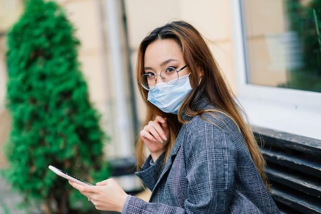 Giovane imprenditrice asiatica con maschera utilizzando il telefono e seduto con la distanza al di fuori della caffetteria