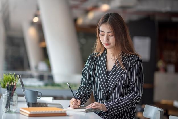 Giovane donna di affari asiatica che lavora al computer portatile e che prende nota mentre sedendosi al tavolo in ufficio