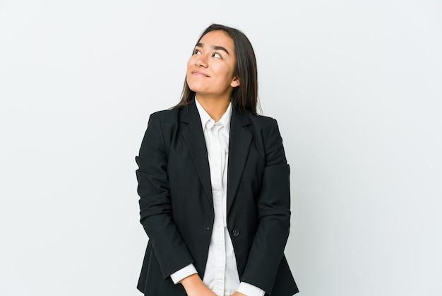 Giovane donna asiatica bussines isolata sul muro bianco che sogna di raggiungere obiettivi e scopi