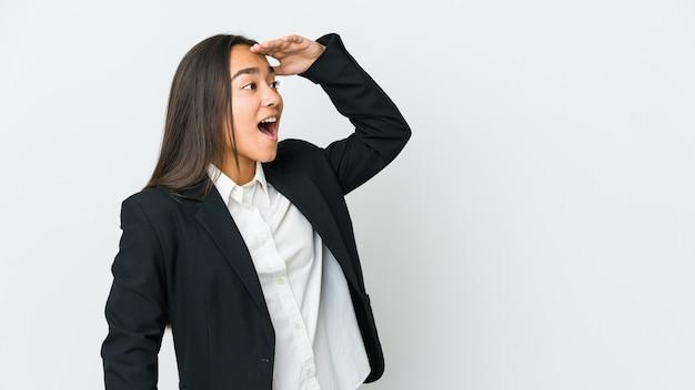 Giovane donna asiatica bussines isolata sul muro bianco che guarda lontano tenendo la mano sulla fronte.